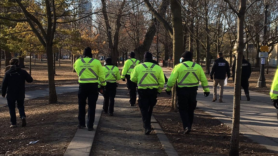 About 9 City Bylaw Enforcement, wearing high visibility vests, and corporate security walk through the park. One guard has papers in his hands.